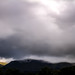 landscape - as heavy clouds roll over and darkness falls the sun is still shining over the Ochil hills in the next valley, Alloa, Clackmannashire, Scotland