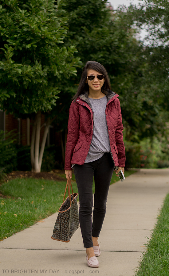 dark red quilted jacket with hood, gray top with front knot, black skinny jeans, patterned tote, light pink drivers