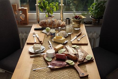Selbstgebackenes Weißbrot zu vom Kalten Buffet übrig gebliebenem Fisch, Käse und Aufschnitt