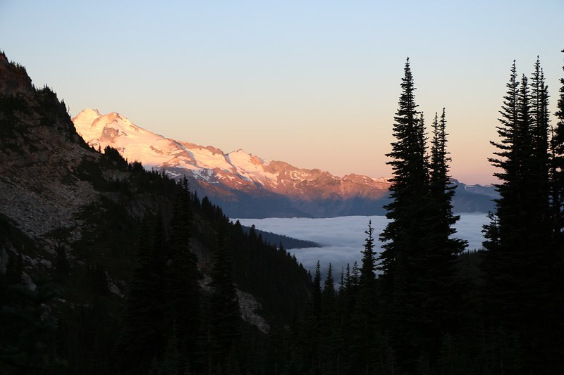 Dawn light shining on Glacier Peak and low clouds filling the valley below from Cloudy Pass