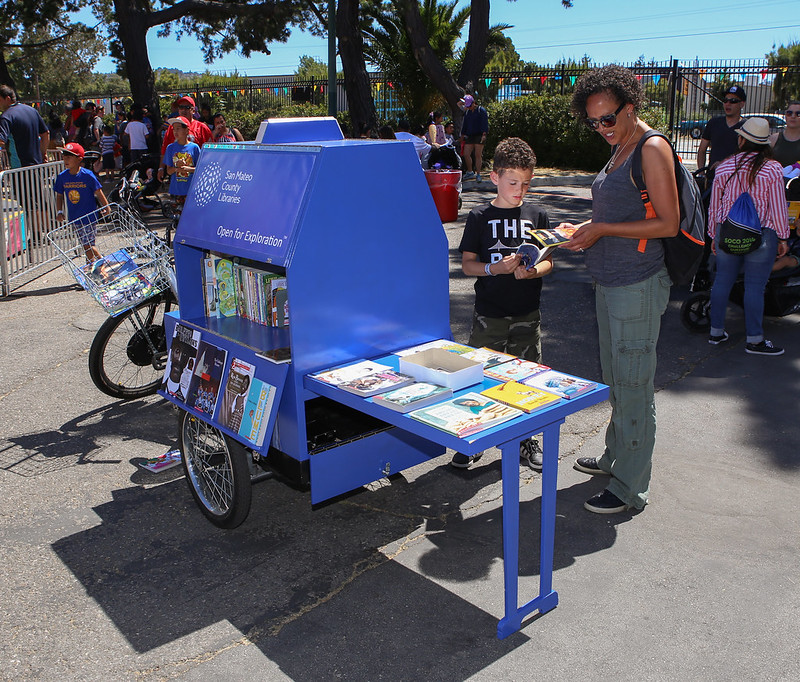 Mom and son looking at books on the book bike.