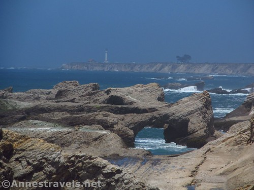 A sea arch and the Point Arena Lighthouse from Point Arena-Stornetta National Monument, California