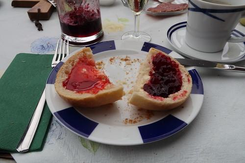 Erdbeermarmelade und Brombeermarmelade auf weißem Brötchen
