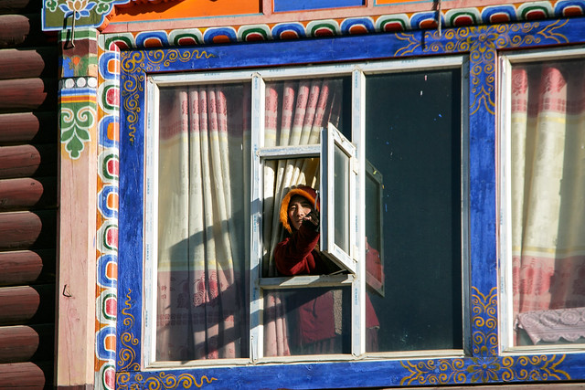 A nun in the colorfully decorated window, Yarchen Gar アチェンガルゴンパ 窓から顔を出す尼僧