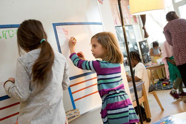 Kindergarteners writing on board
