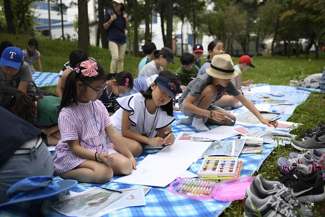 Elementary school girls are sharing their drawings with each other. Photo by © Eugene Cheah/EAAFP
