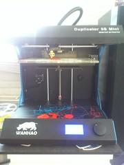 Hier zie je mijn 3D-printer in actie. Links ligt er nog een rol materiaal waarmee ik de onderdelen print. Echter heeft wel iedere rol zijn eigen kleur materiaal.