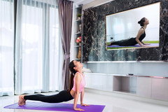 Asian lady start to training Yoga by follow coach in television