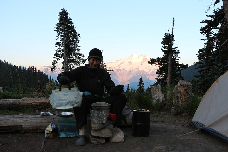 Vicki cooking breakfast with Glacier Peak in the background from our camp at Buck Creek Pass