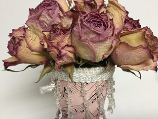 A closeup of a cornucopia of dried pink roses.
