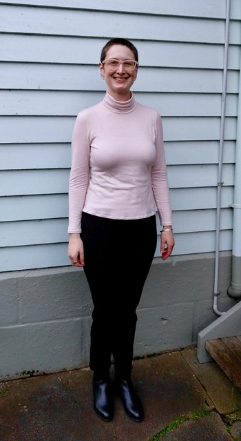 An image of a woman standing in front of a blue weatherboard background. She is wearing a pink merino turtleneck long sleeve tee, black ponte pants, black ankle boots and pink glasses. She is looking at the camera and smiling.