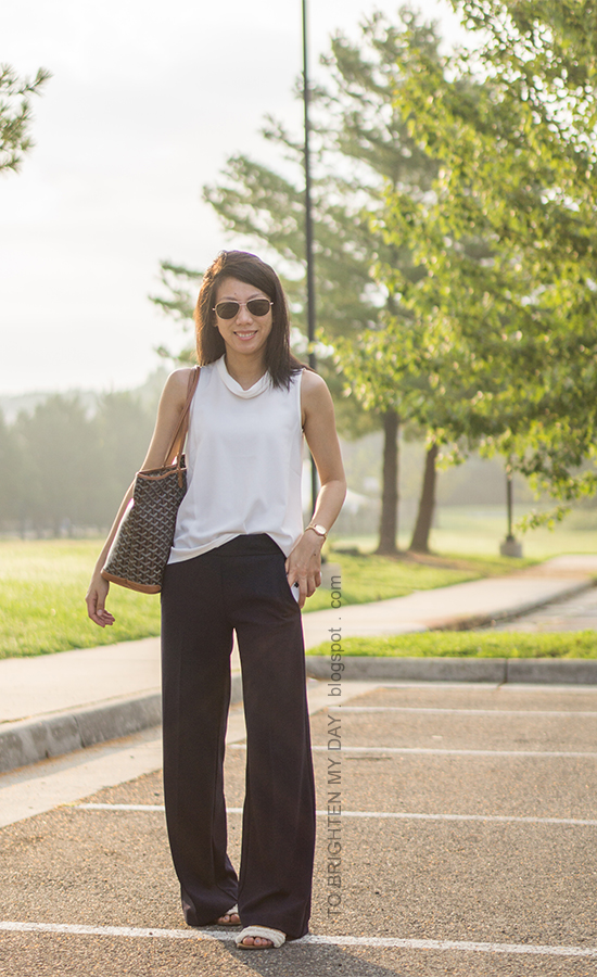white mock neck sleeveless top, navy wide legged pants, gold watch, monogrammed tote, sandals with fringe embellishments