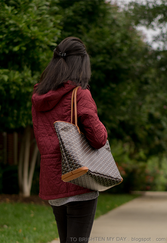 dark red quilted jacket with hood, gray top with front knot, black skinny jeans, patterned tote
