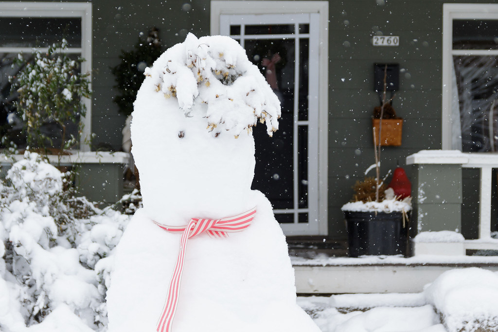 A close-up of a well-dressed snowman on a snowy day
