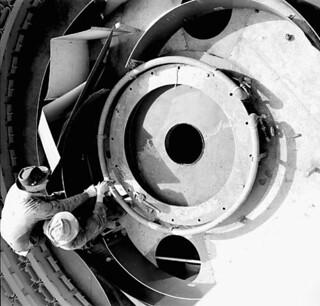 Male pipe fitters install a steam-heating system around the carriage of each gun on an aircraft carrier... / Des tuyauteurs installent un système de chauffage à vapeur autour de l'affût de chaque canon sur un porte-avions...