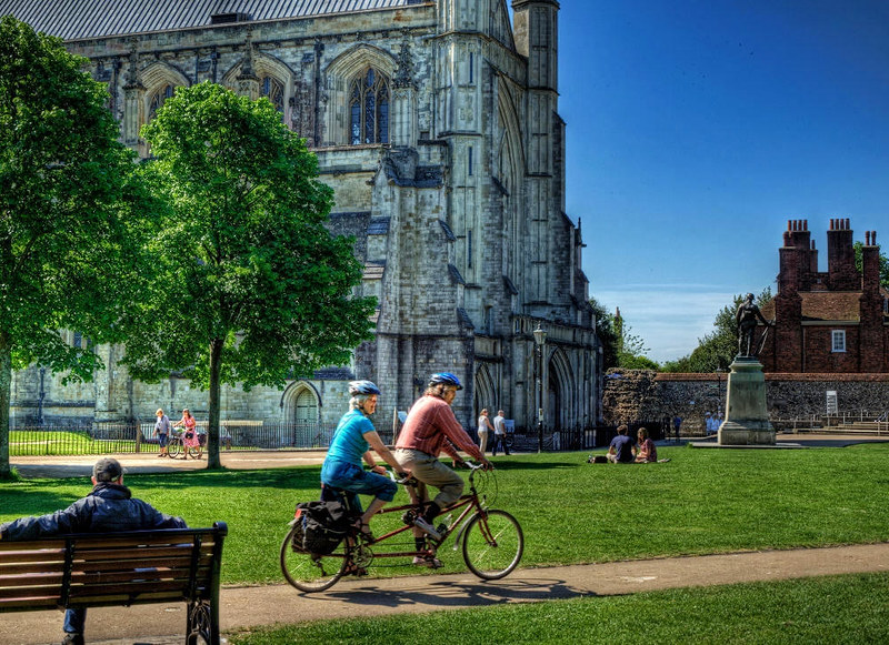 A couple cycle past Winchester Cathedral on a bicycle made for two. Credit Neil Howard, flickr