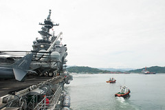 Tugs accompany the USS America (LHA 6) as it departs Malaysia, Aug. 19. (U.S. Navy/MC2 Alexander A. Ventura II)