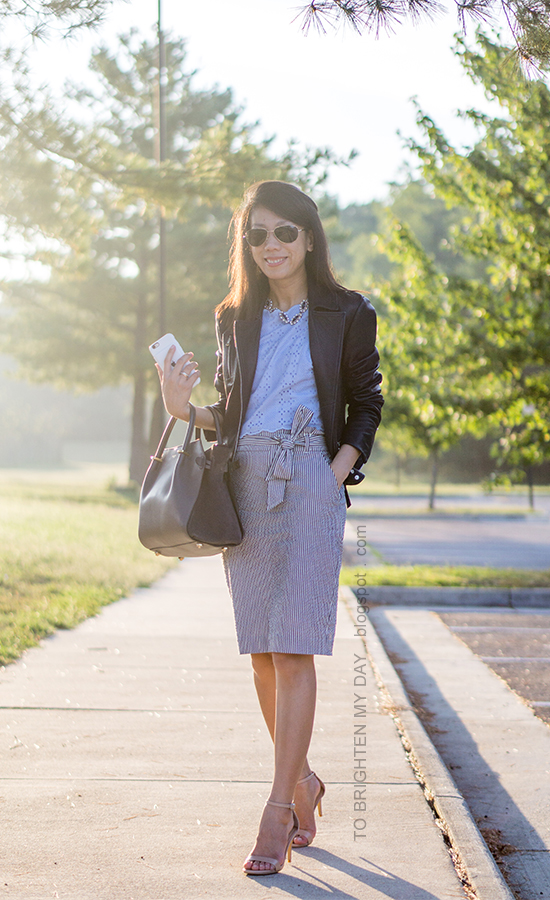 black leather jacket, gemstone necklace, baby blue eyelet cropped top, seersucker pencil skirt with bow tie, gray tote, nude heels