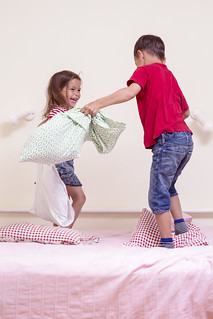 Funny Kids Playing with Pillows on Bedroom. Improvised Children Battel Indoors.