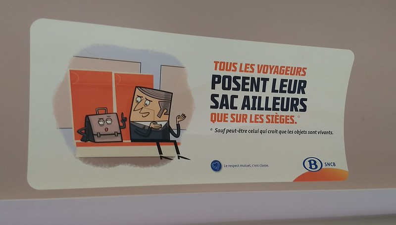 "Belgian train ad. Loosely translated: ""To all travellers, don't put your bag on the seat, unless you believe objects are alive. Mutual respect is class."""