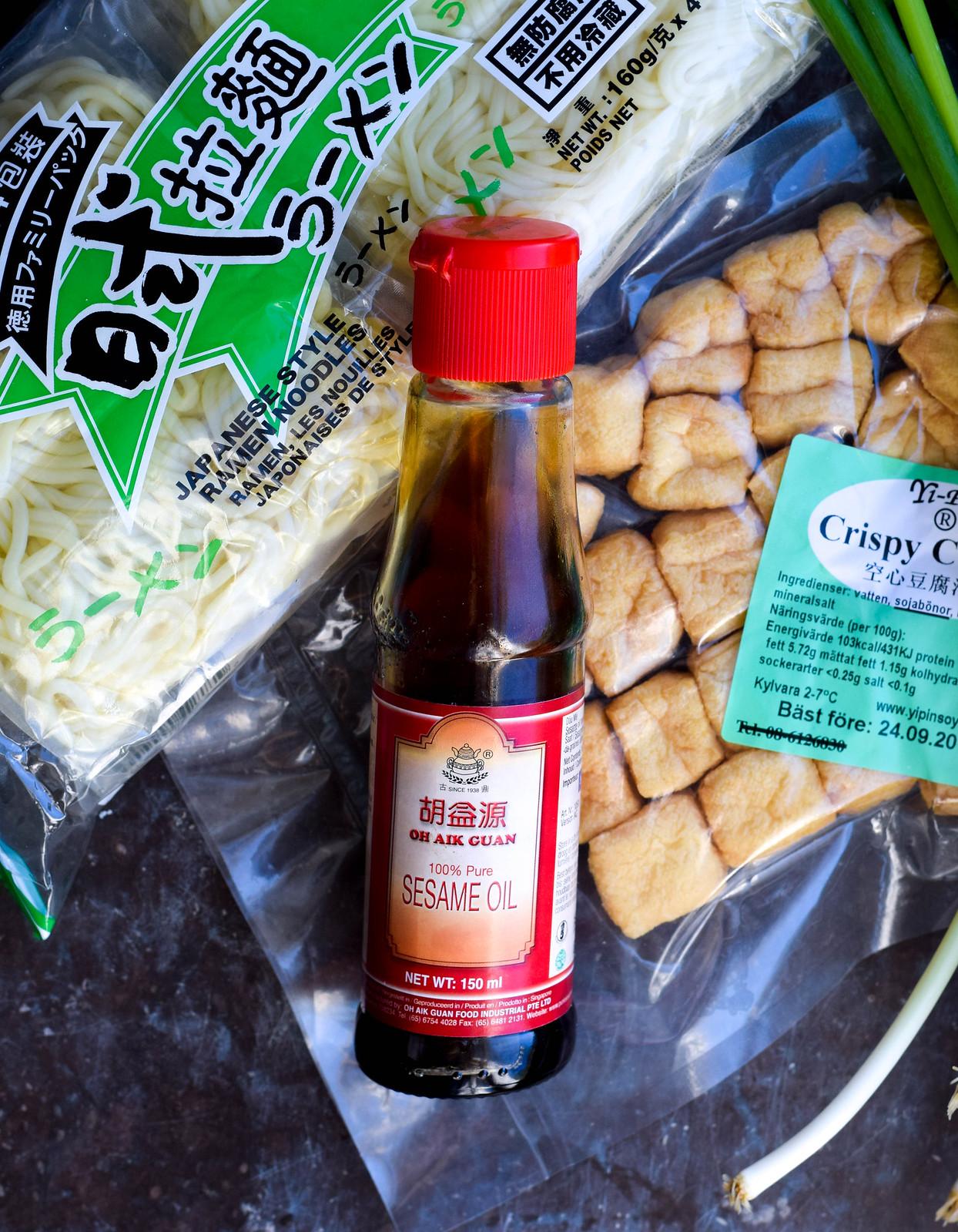Ett paket med färska ramennudlar, tofupuffar, en flask sesamolja och vårlök ligger på ett fönsterbläck i mörk marmor