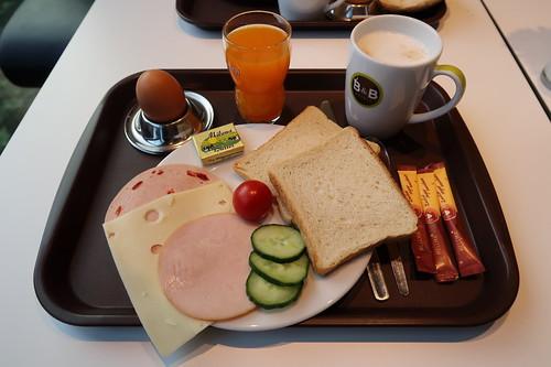 Milchkaffee, Multivitaminsaft, Frühstücksei, Wurstaufschnitt, Scheibenkäse, Butter, Toast, Tomate und Gurkenscheiben