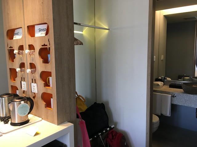 有個功能牆,上面插滿了礦泉水與茶杯,旁邊有衣桿可以掛衣服,還有個行李架可以置物,再過去是廁所@宜蘭捷絲旅礁溪館