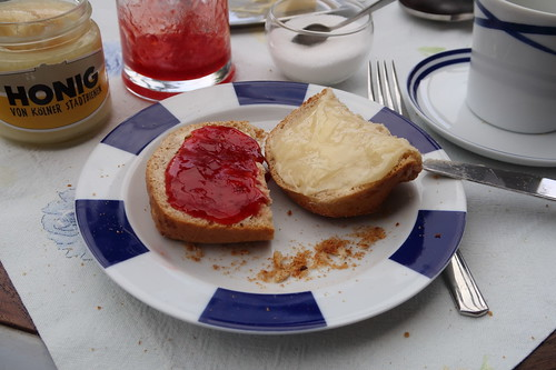 Erdbeermarmelade und Honig auf weißem Brötchen