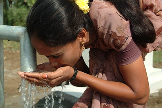 Woman drinking from well.