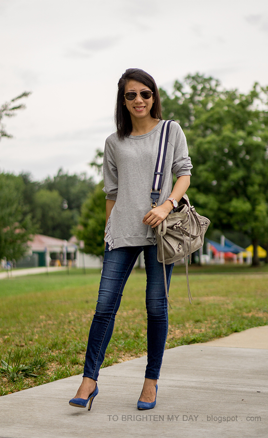 gray ruffle trim sweatshirt, skinny jeans, blue suede pumps, gray tote with navy stripe strap, oversized watch
