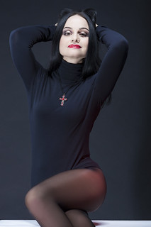Natural Studio Portrait of Sexy and Sensual Caucasian Brunette Woman in Black Body Suit Posing on White Box Against Black Background