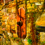Stone wall and iron fixture in the sunshine.
