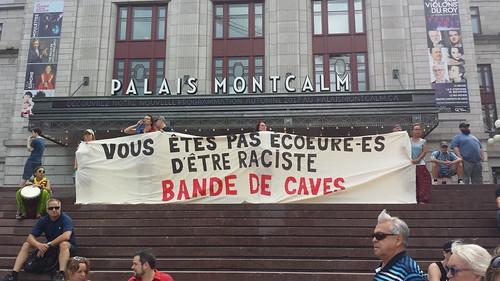 Devant l'écriteau géant « Palais Montcalm », des gens tiennent une énorme bannière se lisant « Vous êtes pas écoeuré-es d'être raciste bande de caves » ; il faut connaître la référence, soit la phrase « Vous n'êtes pas tannez de mourir bande de caves » qui fait partie de l'art permanent du Grand Théâtre de Québec.