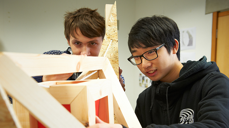 Two students working on a timber frame model