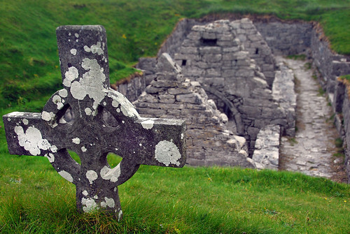 Celtic cross in front of a sunken stone church on the Aran Island of Inisheer in Ireland