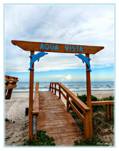 aquavista mysteryname ormondbytheseaflorida beach walkway sign railing sand water ocean atlanticocean sky clouds coastal florida