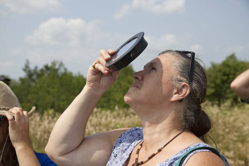 solar eclipse - woman with filtering lens