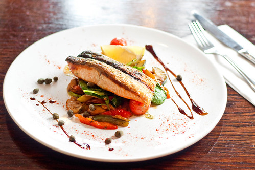 Overview of plate of delicious fish with vegetables at a fancy restaurant