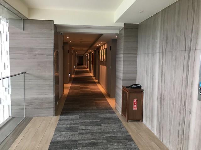 電梯上樓以後,中間是引進採光的天井,走道寬闊,牆上掛了許多琉璃飾品。@屏東恆春墾丁怡灣渡假酒店