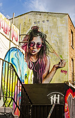purple glasses girl and moon face on a Camden wall