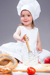 Food Concepts. Glad and Smiling Caucasian Girl In Cook Uniform Making a Mix of Flour, Eggs and Vegetables With Whisk In Studio Environment.
