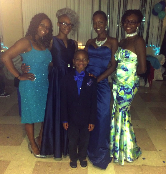 A photo of Ms. Lewis and her family, smiling together, at a formal event.