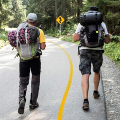 "Men with backpacks are walking along the road. Road sign ""winding road"""