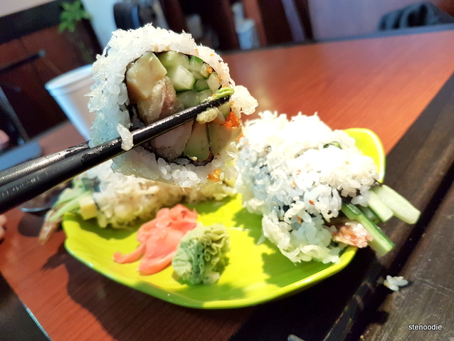 Chopstick holding up Dynamite Roll