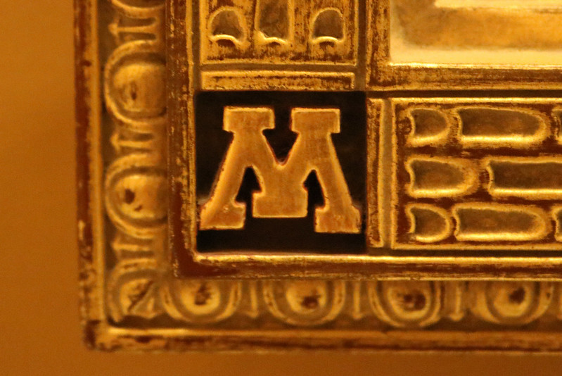 the University of Minnesota's M logo from the bottom left corner of the frame