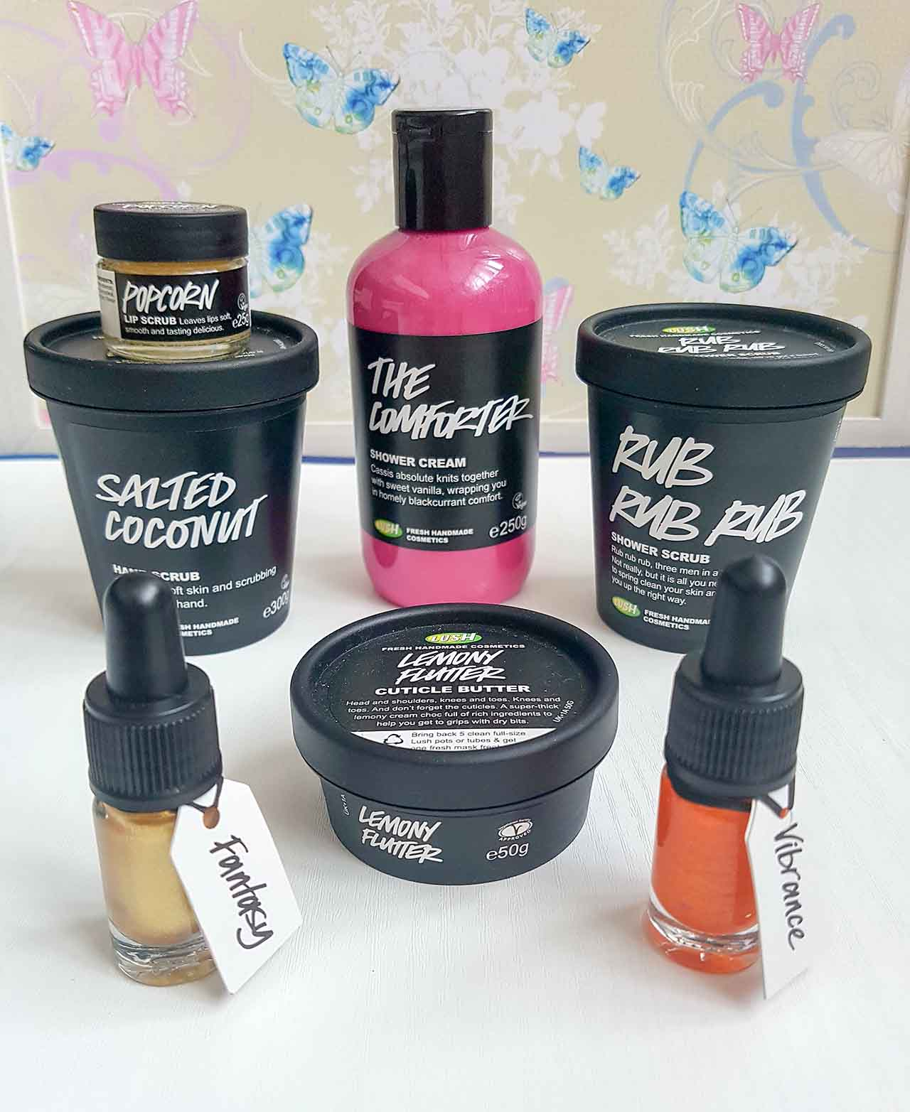 Lush Fresh Handmade Cosmetics – How Lush Are They: I had a proper look around a Lush store only recently and it was a treasure trove of beautiful scents, colours and textures! Lush provides ranges for body, hair and face, and also has makeup and perfume products. They cater for all skin types and needs and have some truly weird and wonderful ingredient combinations! As I wondered around the store I decided it was time to pick up a few items to test and purchased the following. From back to front I bought a Popcorn Lip Scrub, a Salted Coconut Hand Scrub, The Comforter Shower Cream, the Rub, Rub, Rub Shower Scrub, a gold eyeliner called Fantasy, the Lemon Flutter Cuticle Butter and an orange lipstick called Vibrance. Since buying them, I have used each item a number of times and absolutely love them! My reviews on each are below.