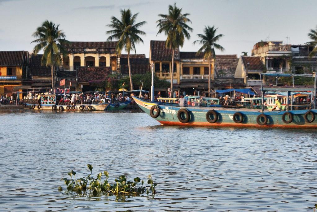 Maisons basses et bateaux à fond plat à Hoi An au Vietnam.