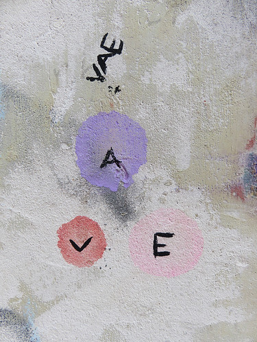 Plaster wall texture with letters and pink and purple dots in Rouen, France