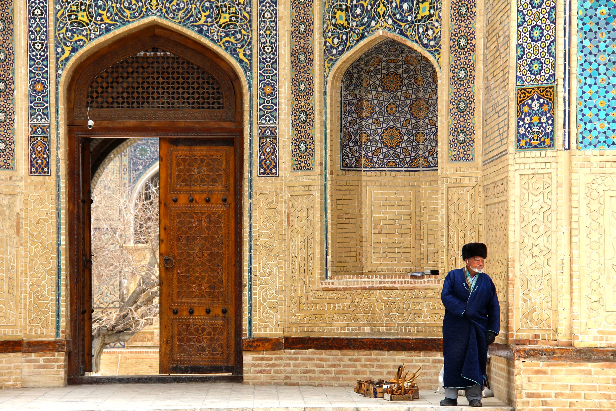 An elder sells his wares outside the stunning Kalyan Mosque in Bukhara, Uzbekistan