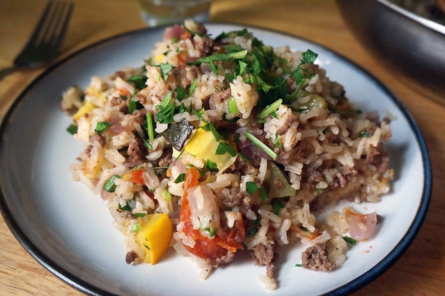 A serving of pilaf piled in the middle of a plate, looking almost magazine-like in warm, soft-focus light.